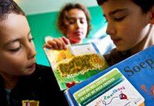 Kinderen tonen boeken die zij samen met oud-minister Gerrit Zalm hebben overhandigd aan de Voedselbank Nederland (2012).